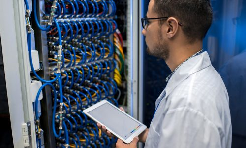 Portrait of young man holding digital tablet standing by supercomputer server cabinets in data center